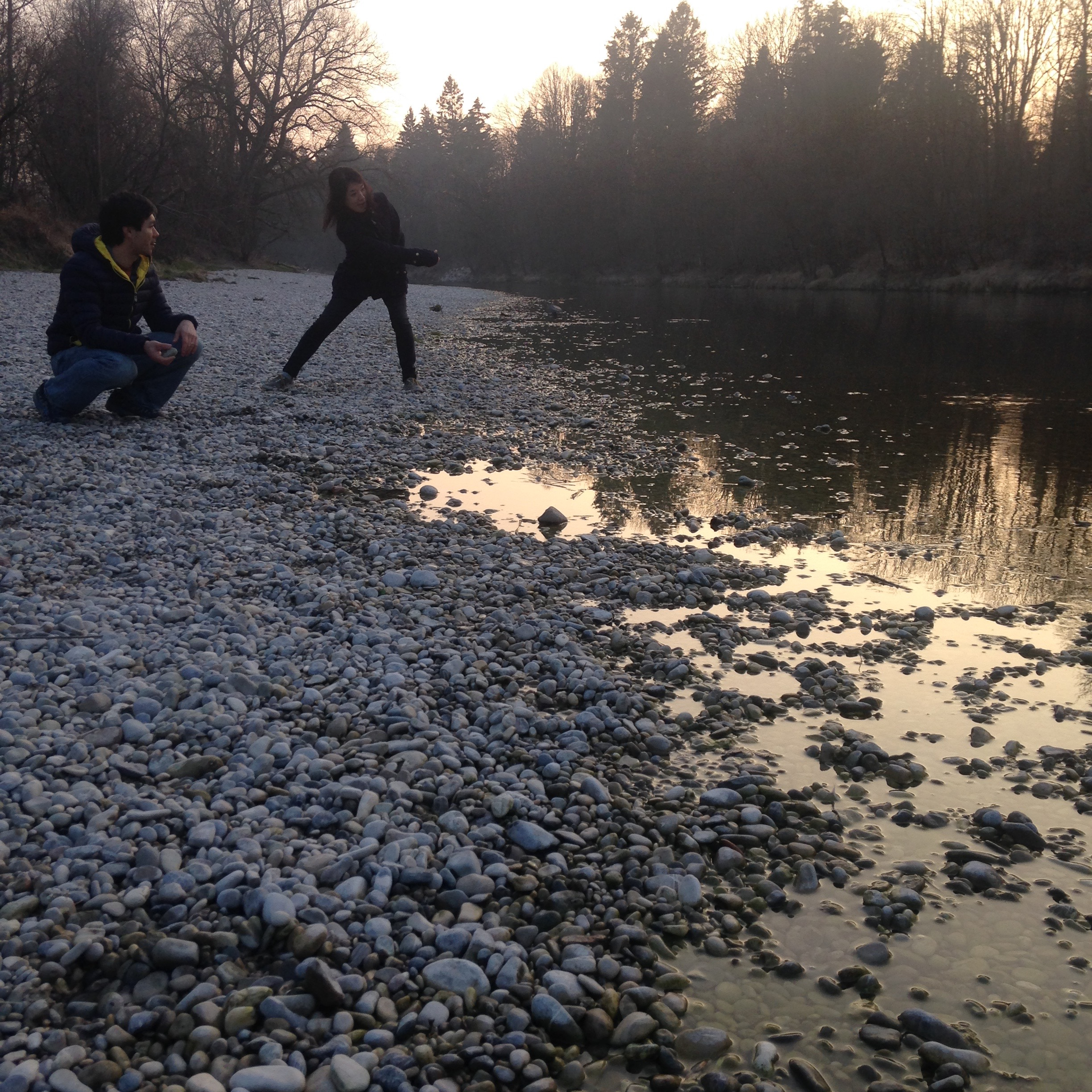 Skipping rocks on the river with friends.