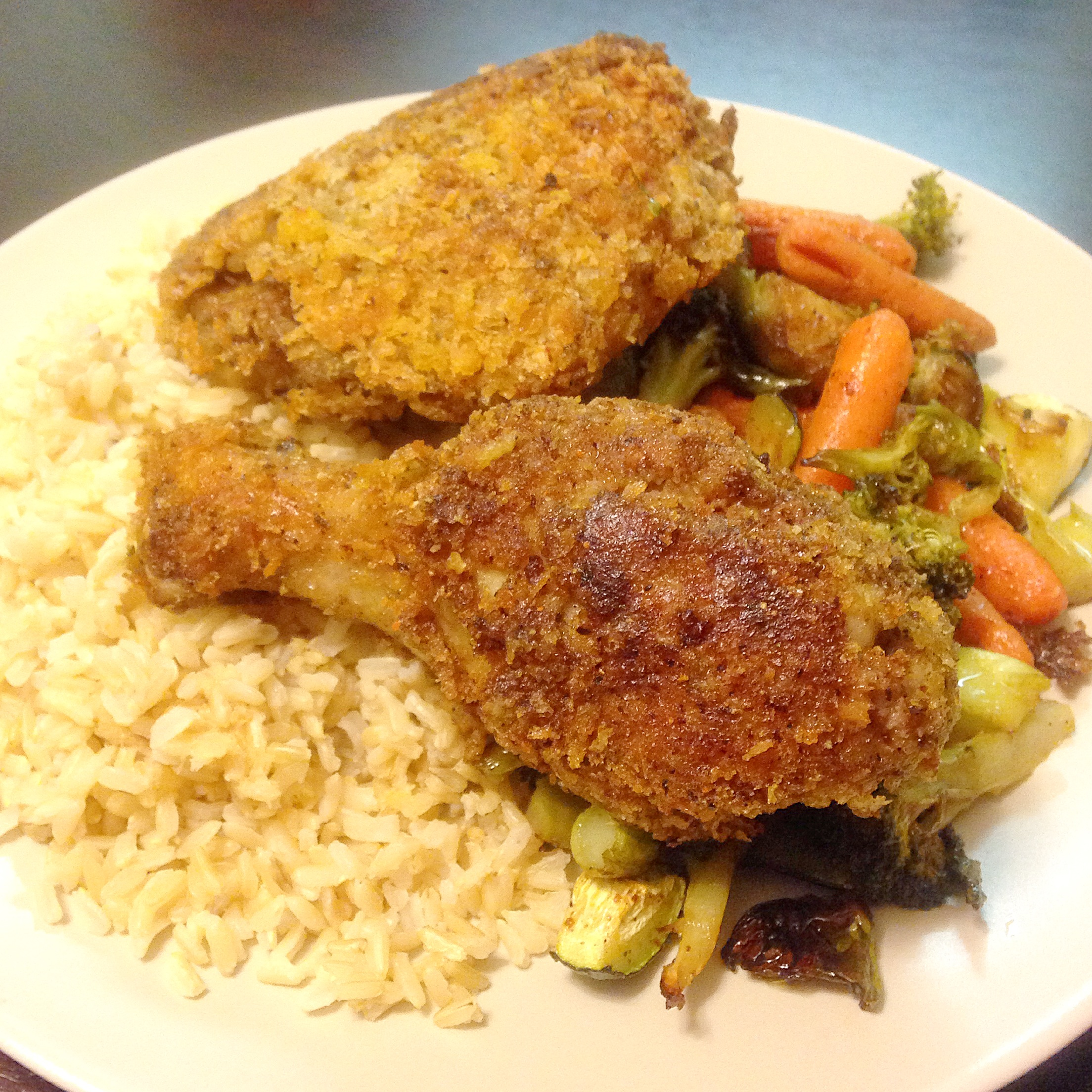 Fried Jamaican Jerk Chicken battered in Panko and Kix Cereal atop brown rice and roasted vegetables.