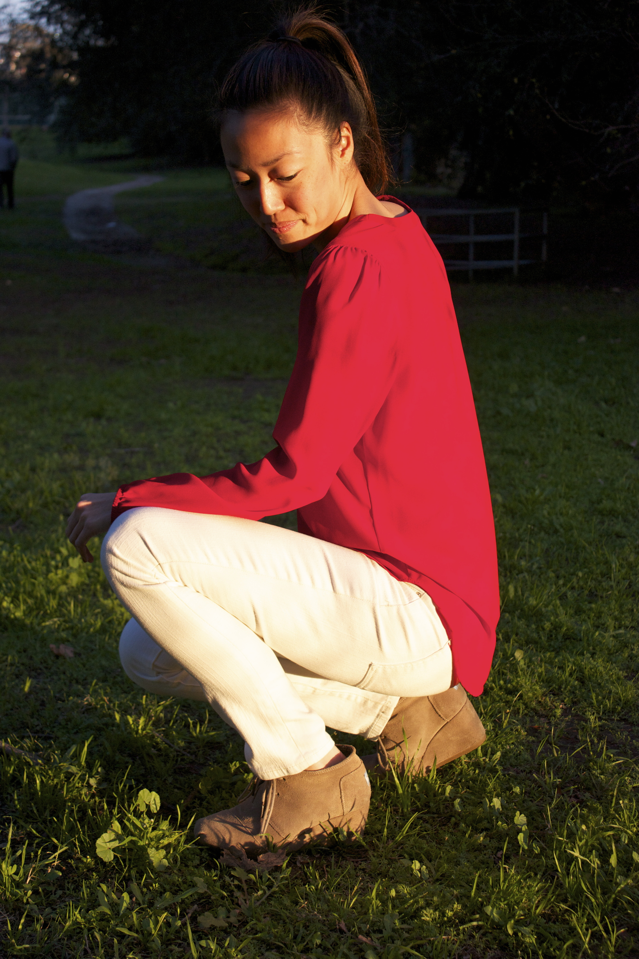 red shirt white jeans squatting