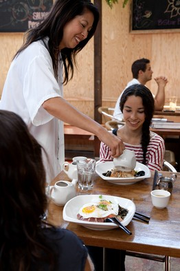 Executive chef Joyce Lee pours tea over a fish dish for customer Ava Martinez at B Star Bar.