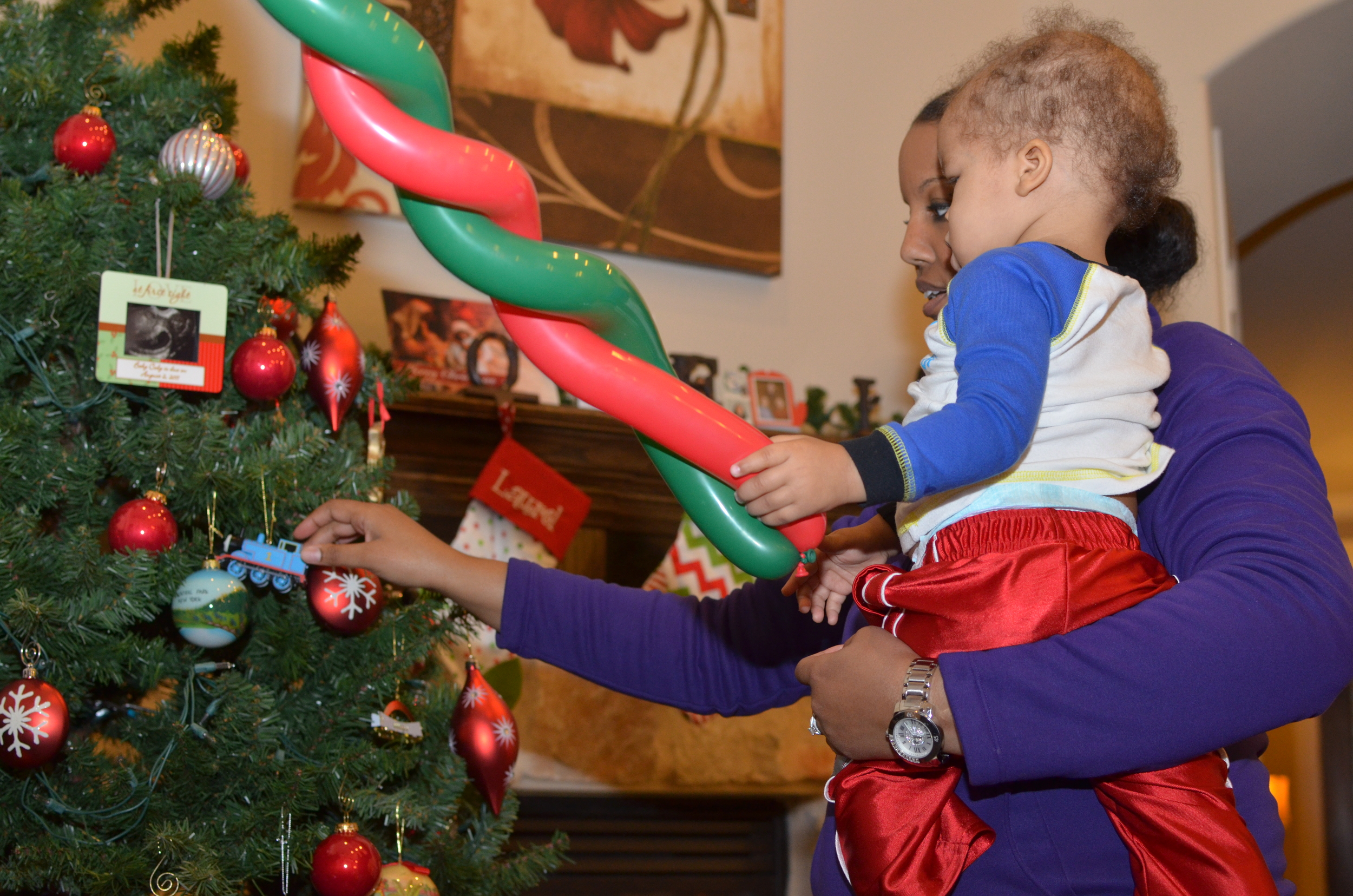 Day 136: Elliott puts his ornament on the tree with some assistance from mom