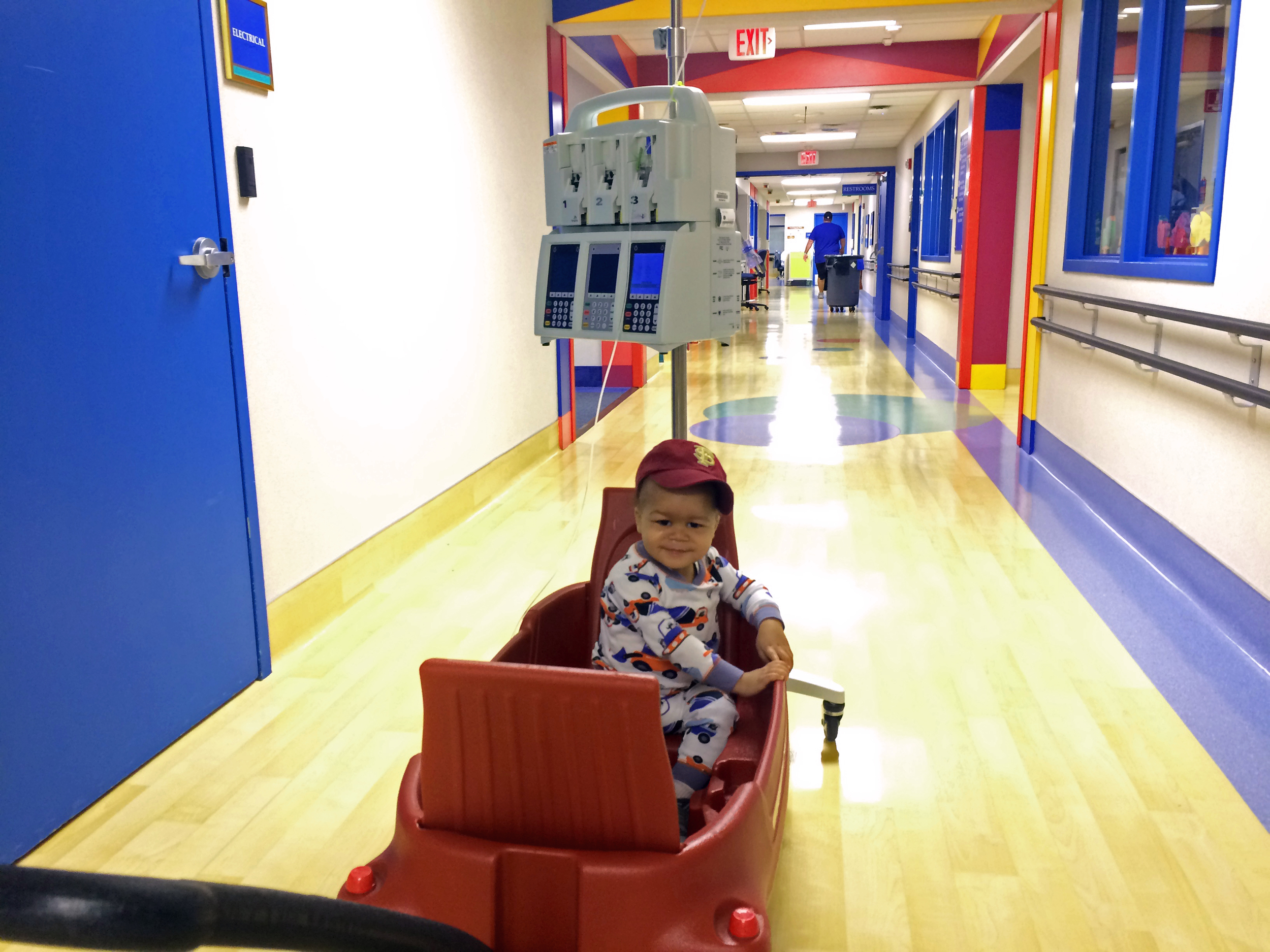 Day 205: Elliott takes a wagon ride around the oncology floor. This has become one of hisfavorite activities. A nurse showed Rachel how to tie the IV pole to back of the wagon to free up one hand.