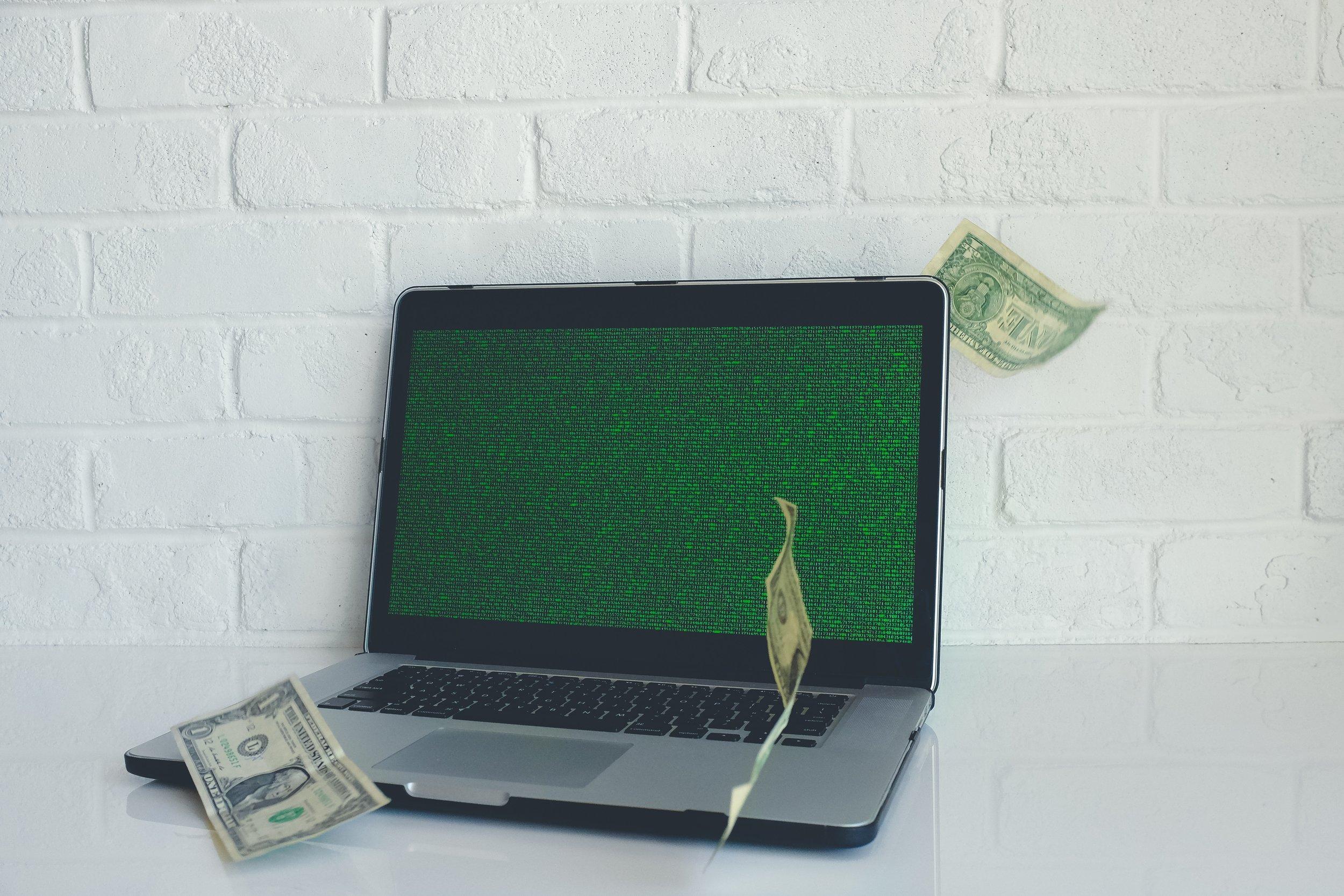 laptop sa zelenom podlogom i novcem.jpg