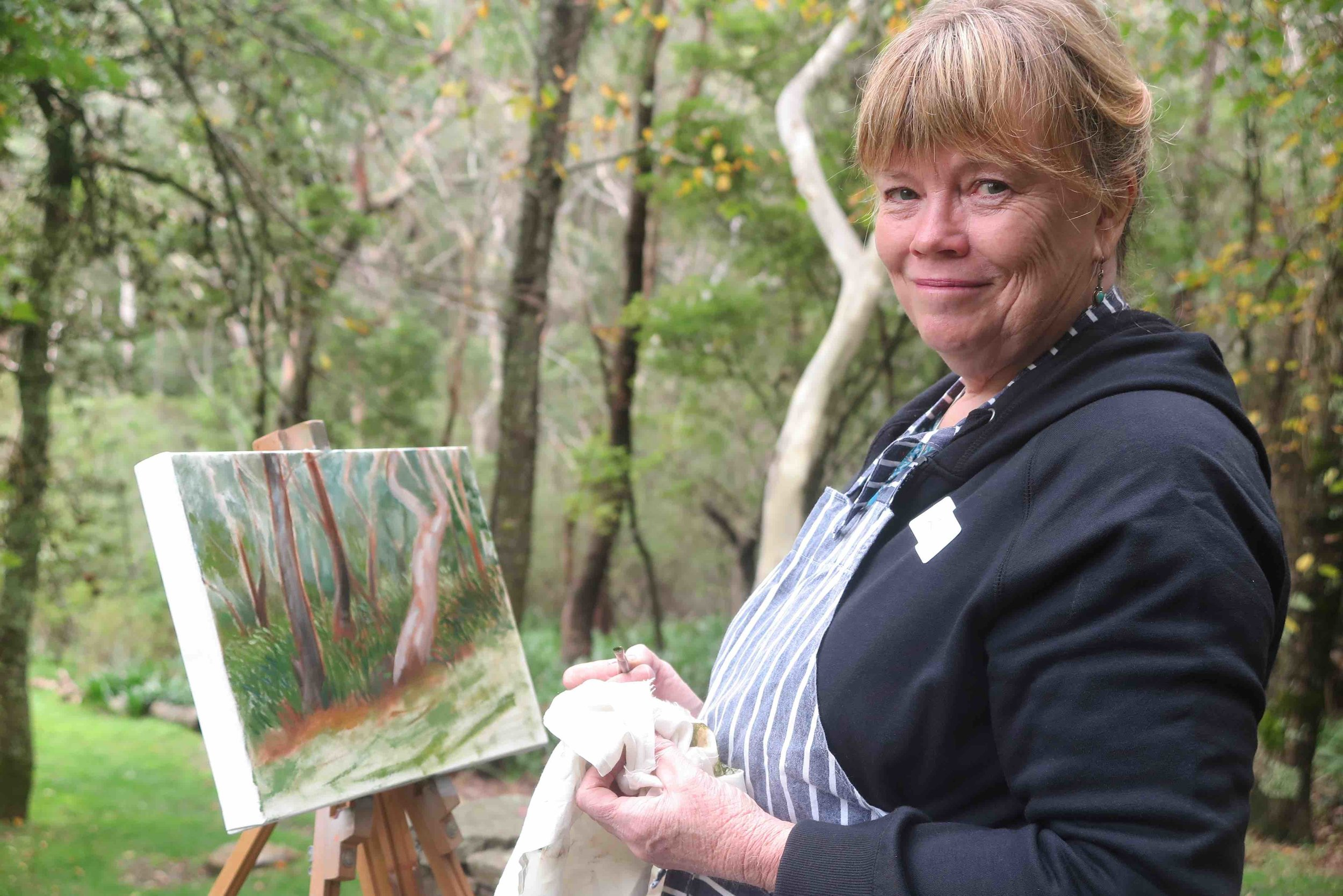 small Winmalee resident, Sue with her 'in progress' oil painting of the bush beyond the garden.jpg