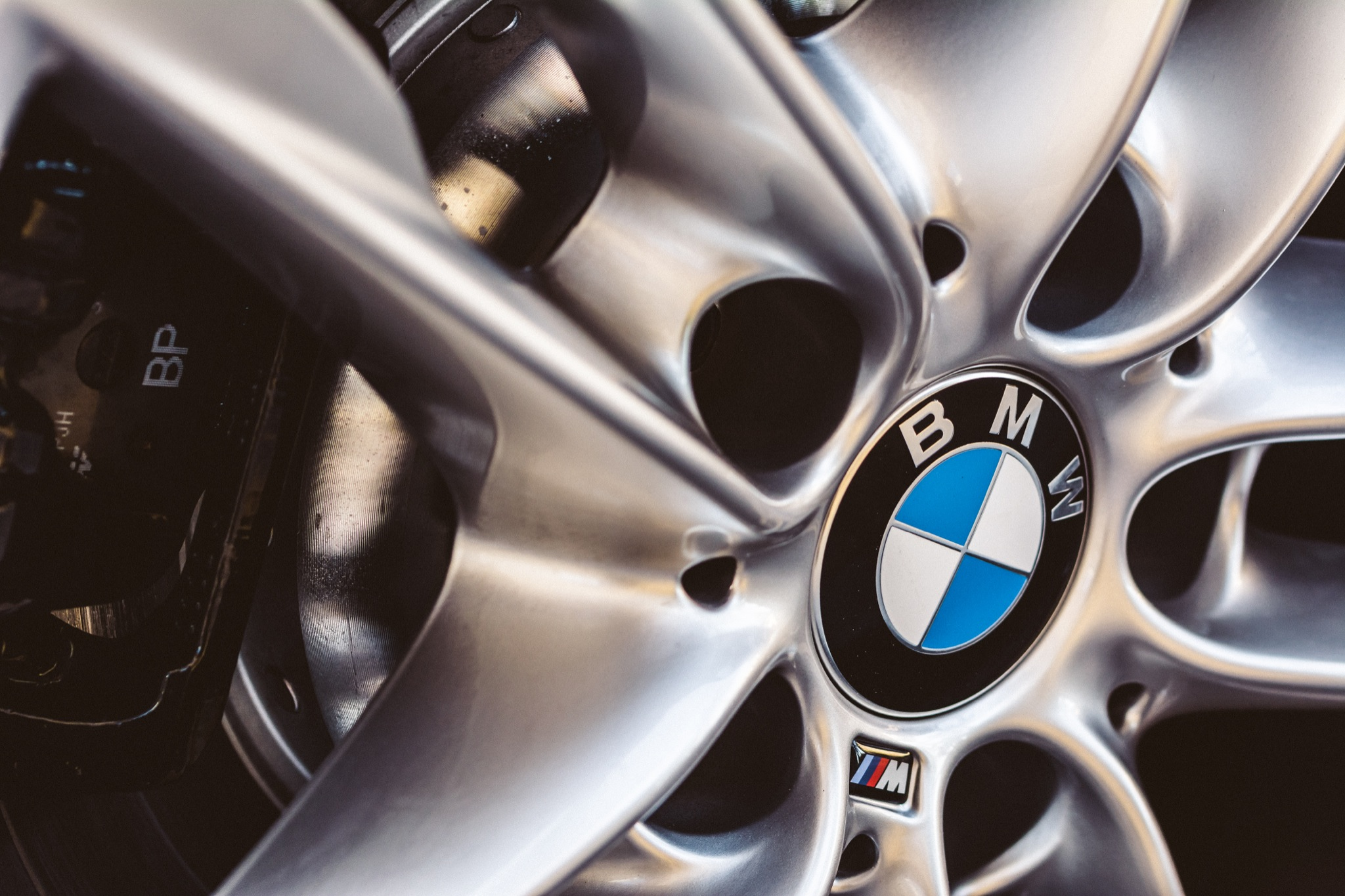 Hubcap and logo from a BMW with details of the brake calipers