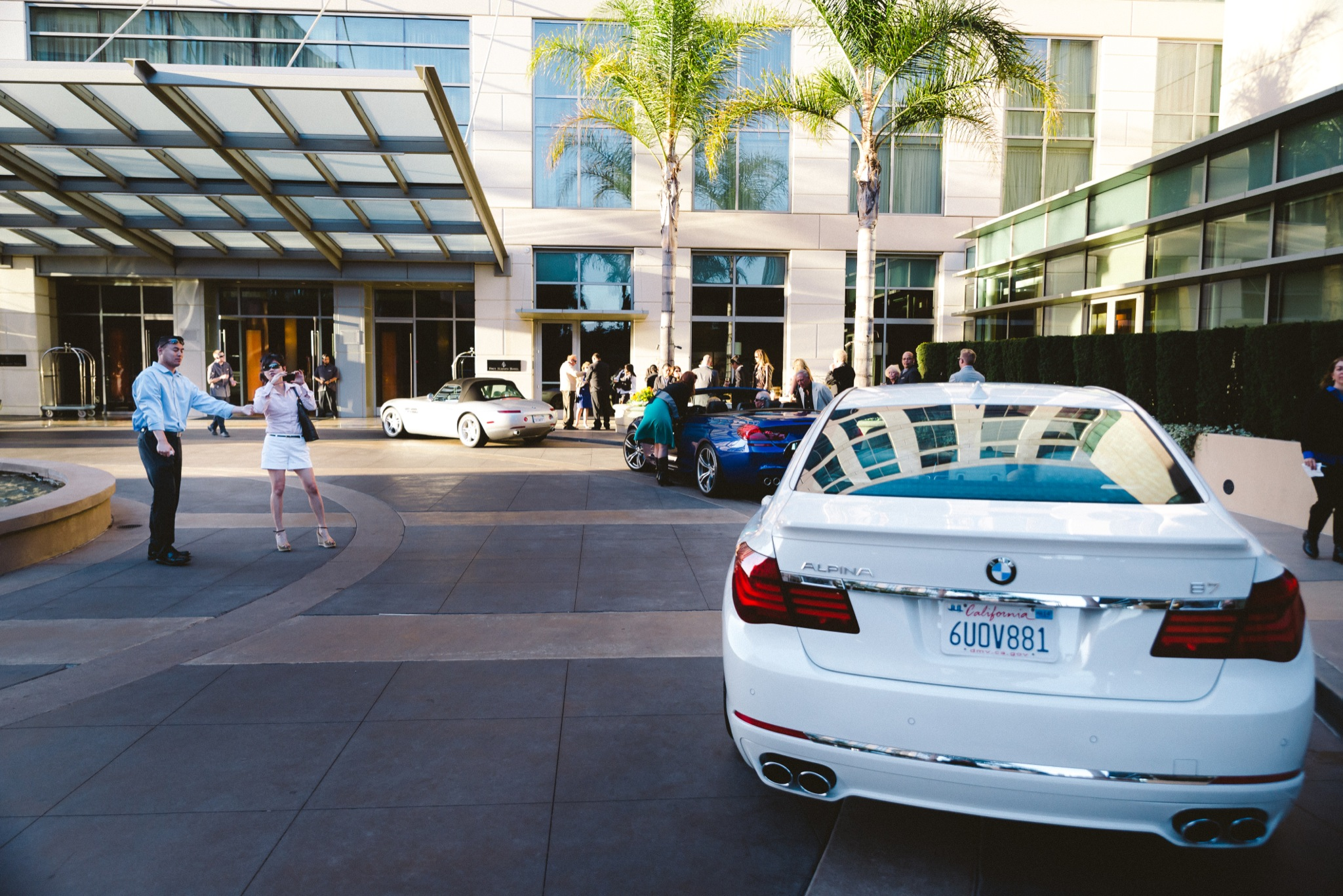 Woman in skirt photographing a white BMW