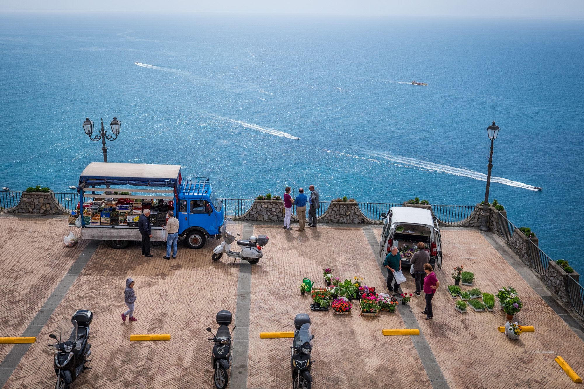 ITALY, Praiano: People gather at a market as boats sail past in the Mediterranean Sea.