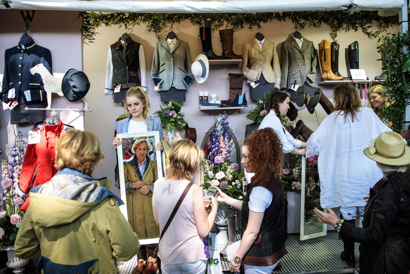 Visitors try-on and purchase clothes at a stall at the Chelsea Flower Show on May 25, 2017 in London.