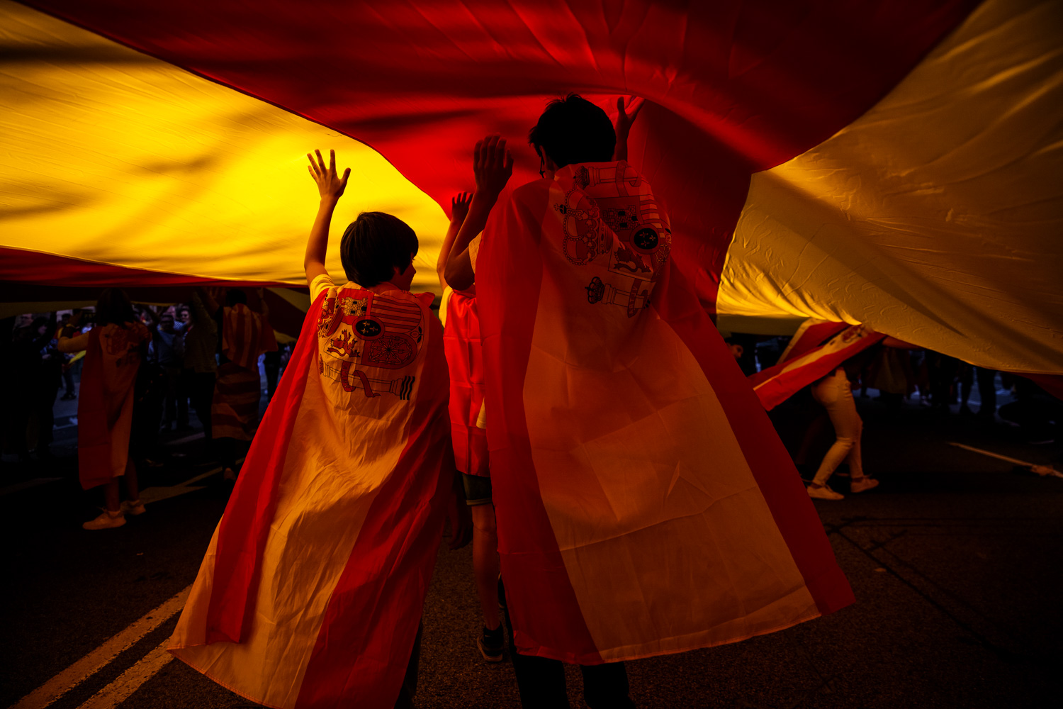 Barcelona, Spain - Young protesters draped in Spanish flags run under a giant Catalan flag during a pro-unity demonstration, 2017.