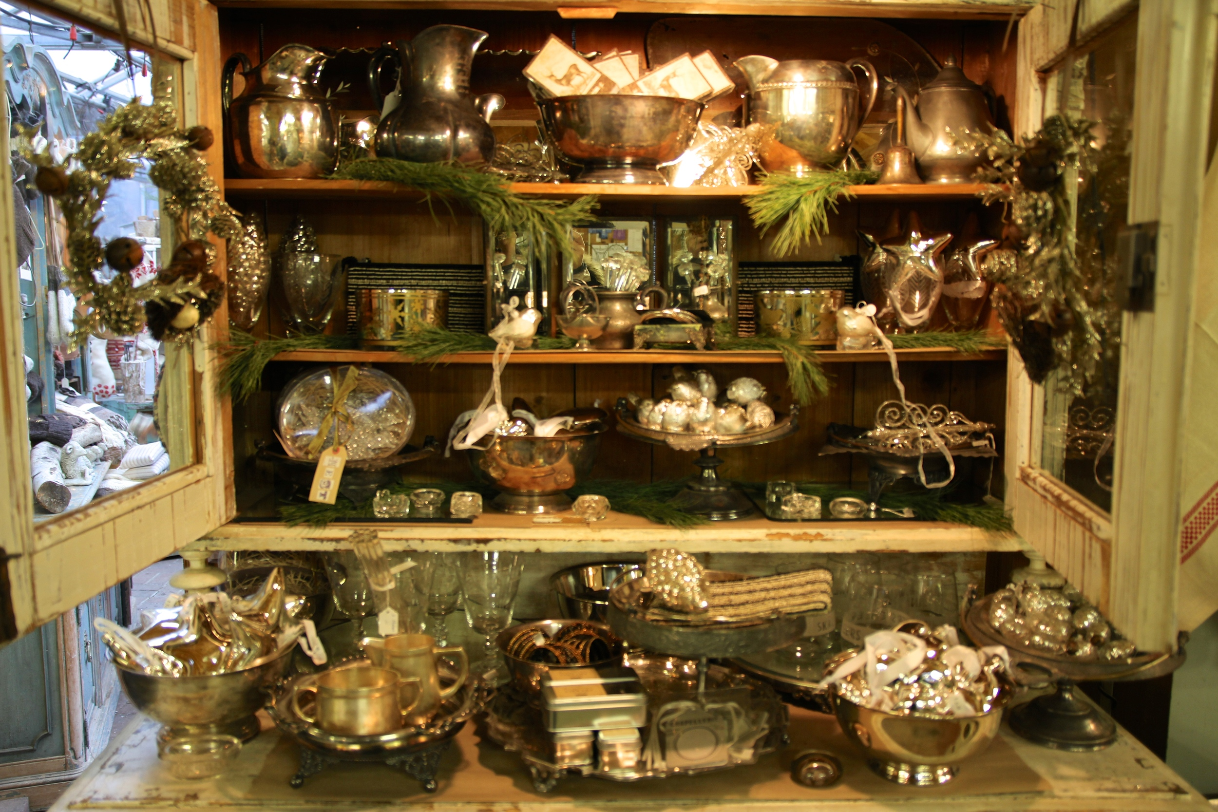 {A cupboard filled to the brim with holiday silver}