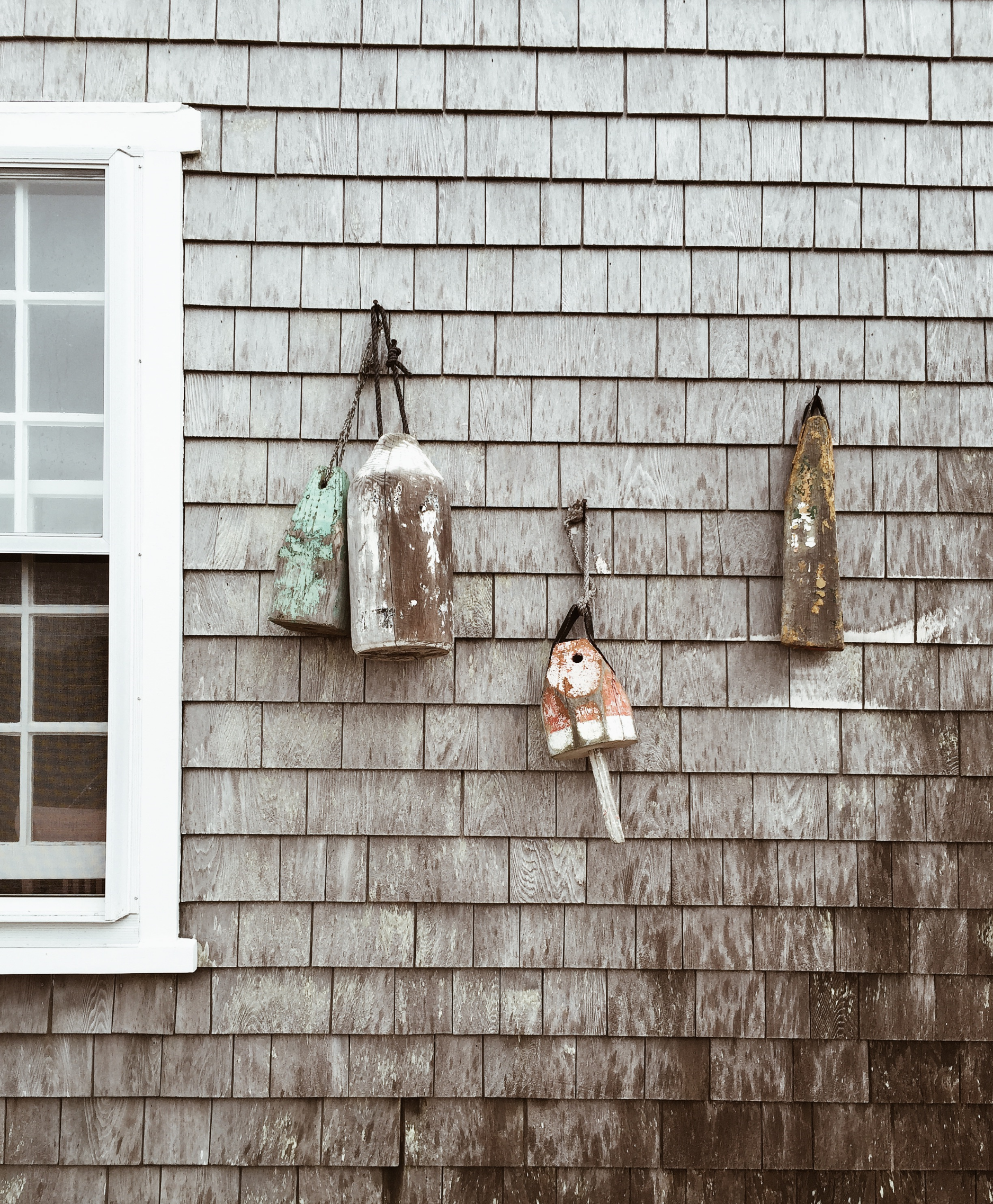 {Love all the textures in this shot of buoys hung on the side of a house}