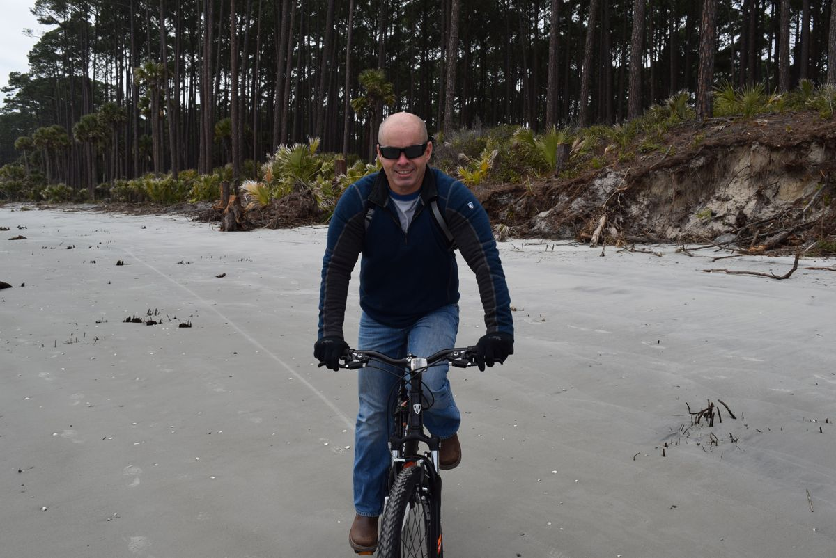 Paul riding his bike on the beach.