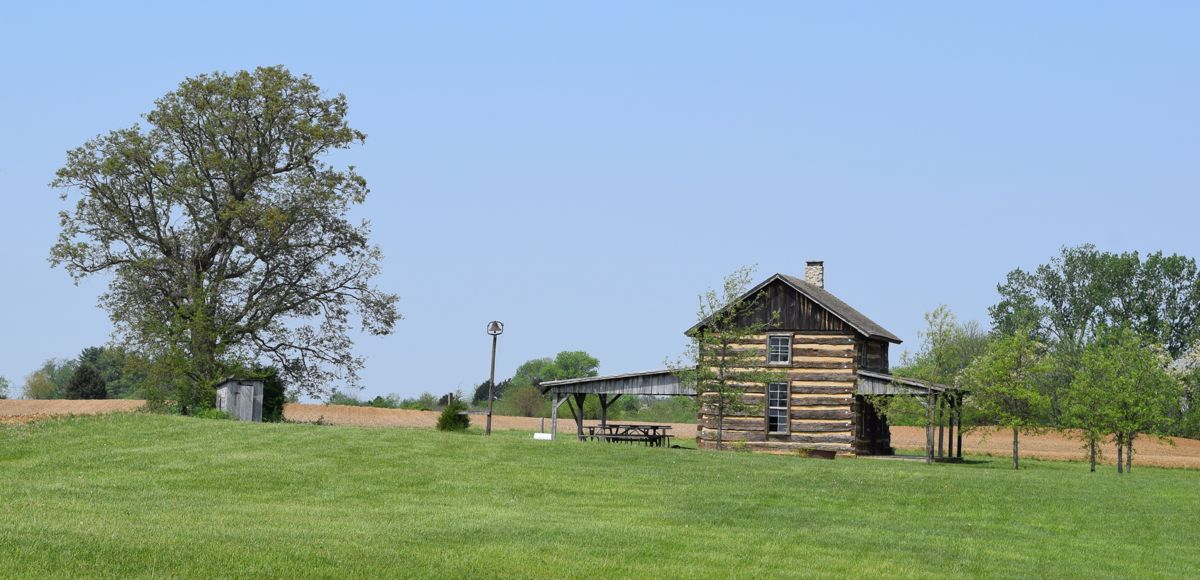 A nicely preserved homestead. Notice the large bell on the pole and the outhouse over by the big tree.