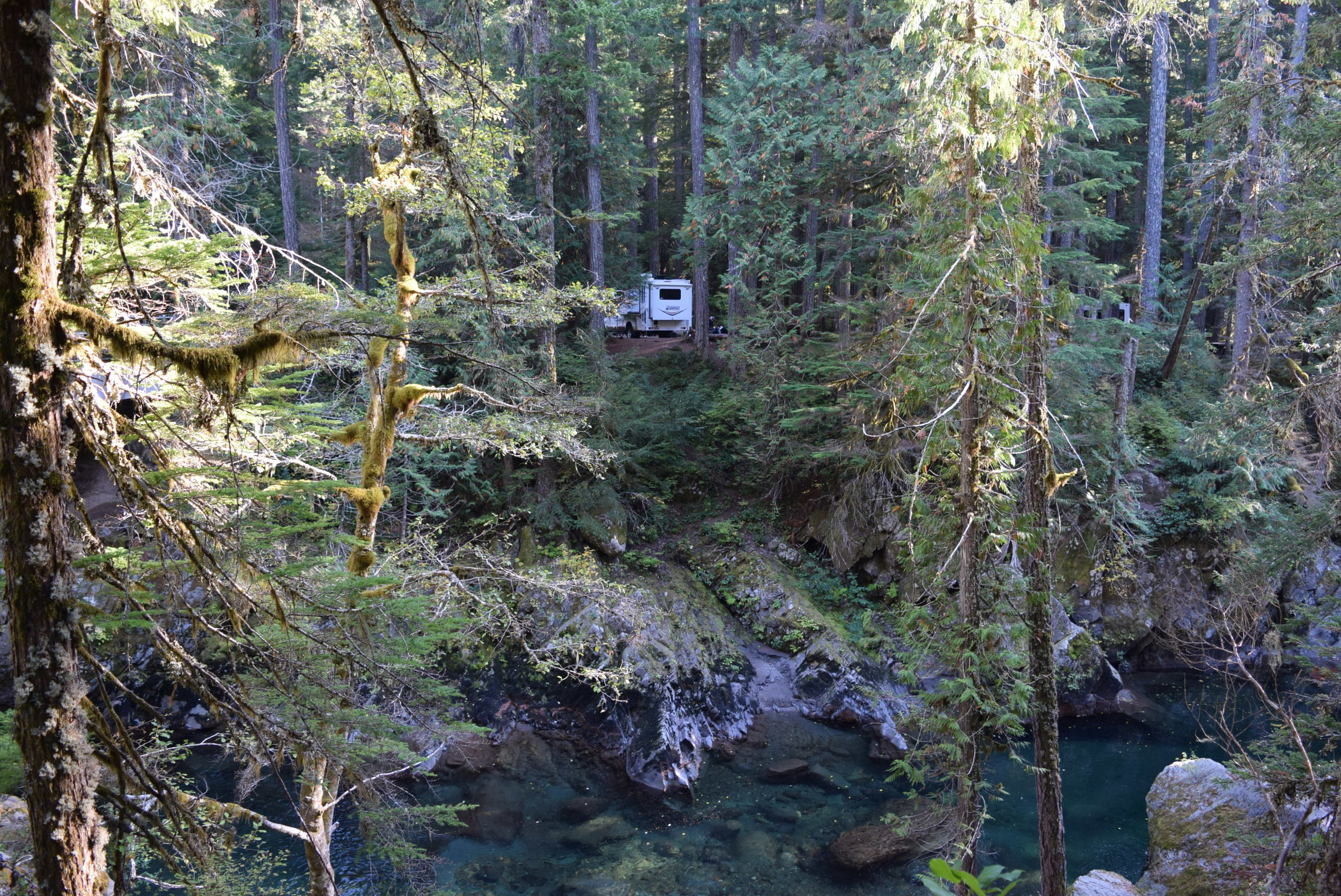 The camper nestled in the woods, above the Ohanapecosh River. Check out the clear water!