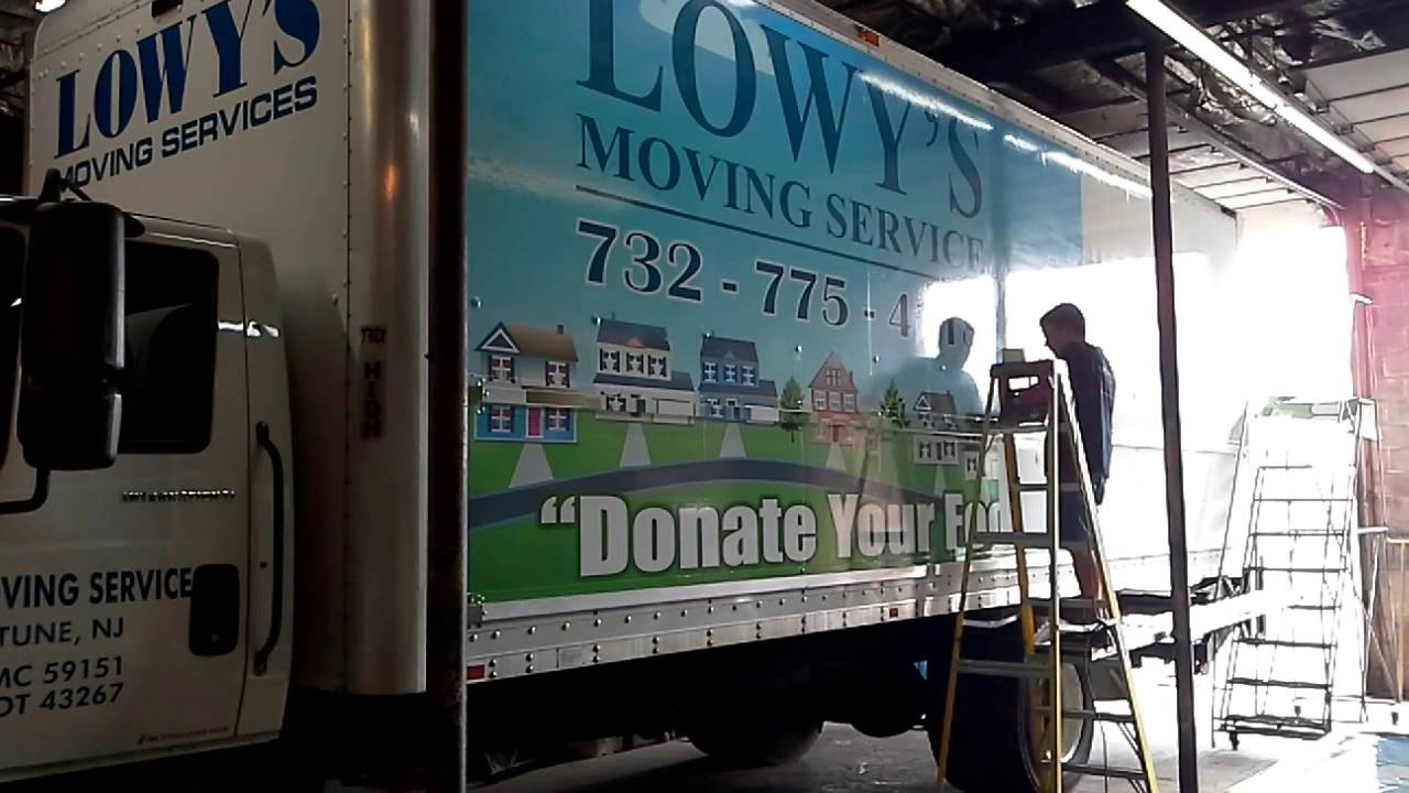 A Lowy's Moving & Storage truck receiving a Move For Hunger facelift