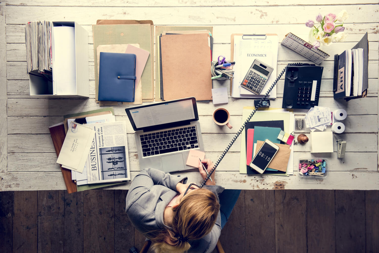 woman working at cluttered desk - why real estate agents need assistants