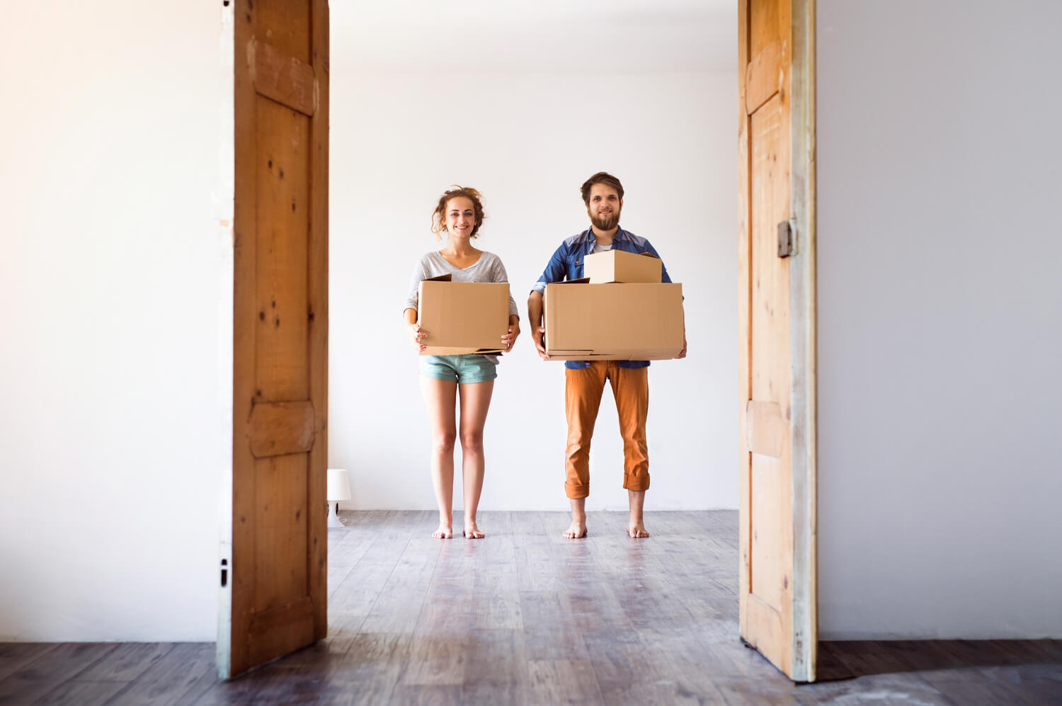 young couple holding boxes - handling difficult real estate clients