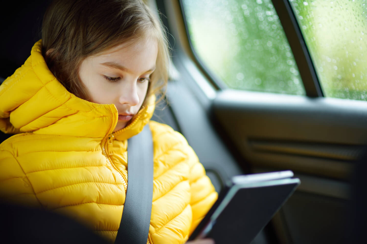 kid reading in car - tips for moving with kids