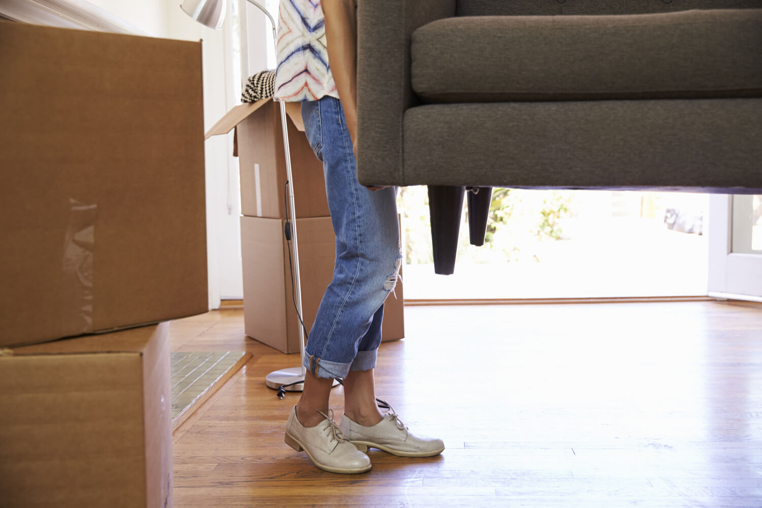 woman lifting couch - multifamily moving tips