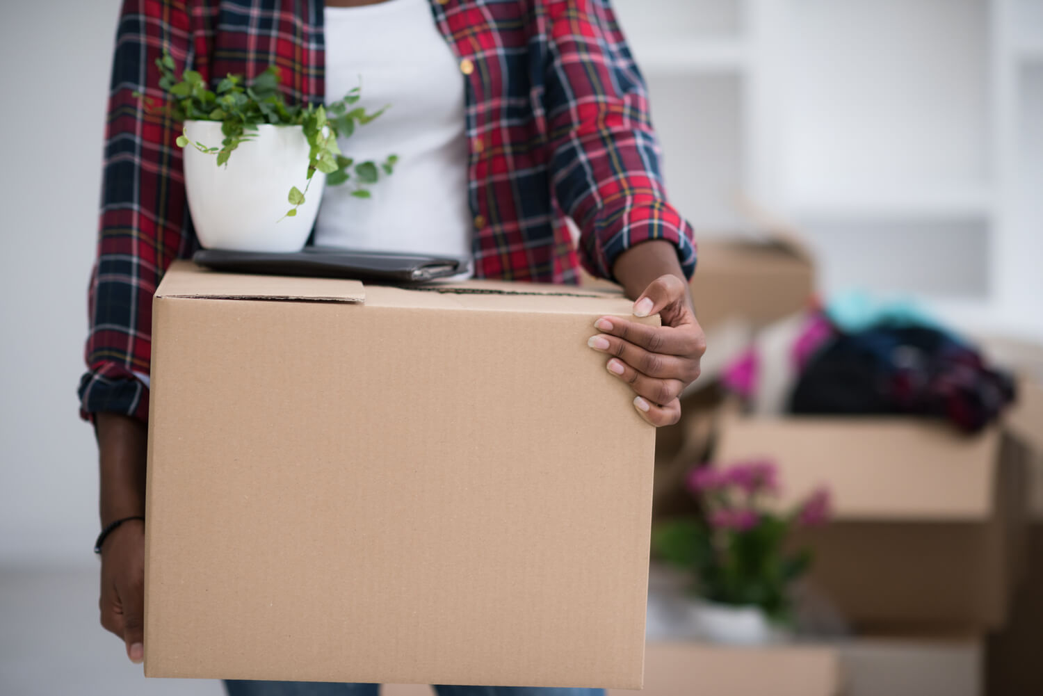 woman holding box - what not to pack when moving
