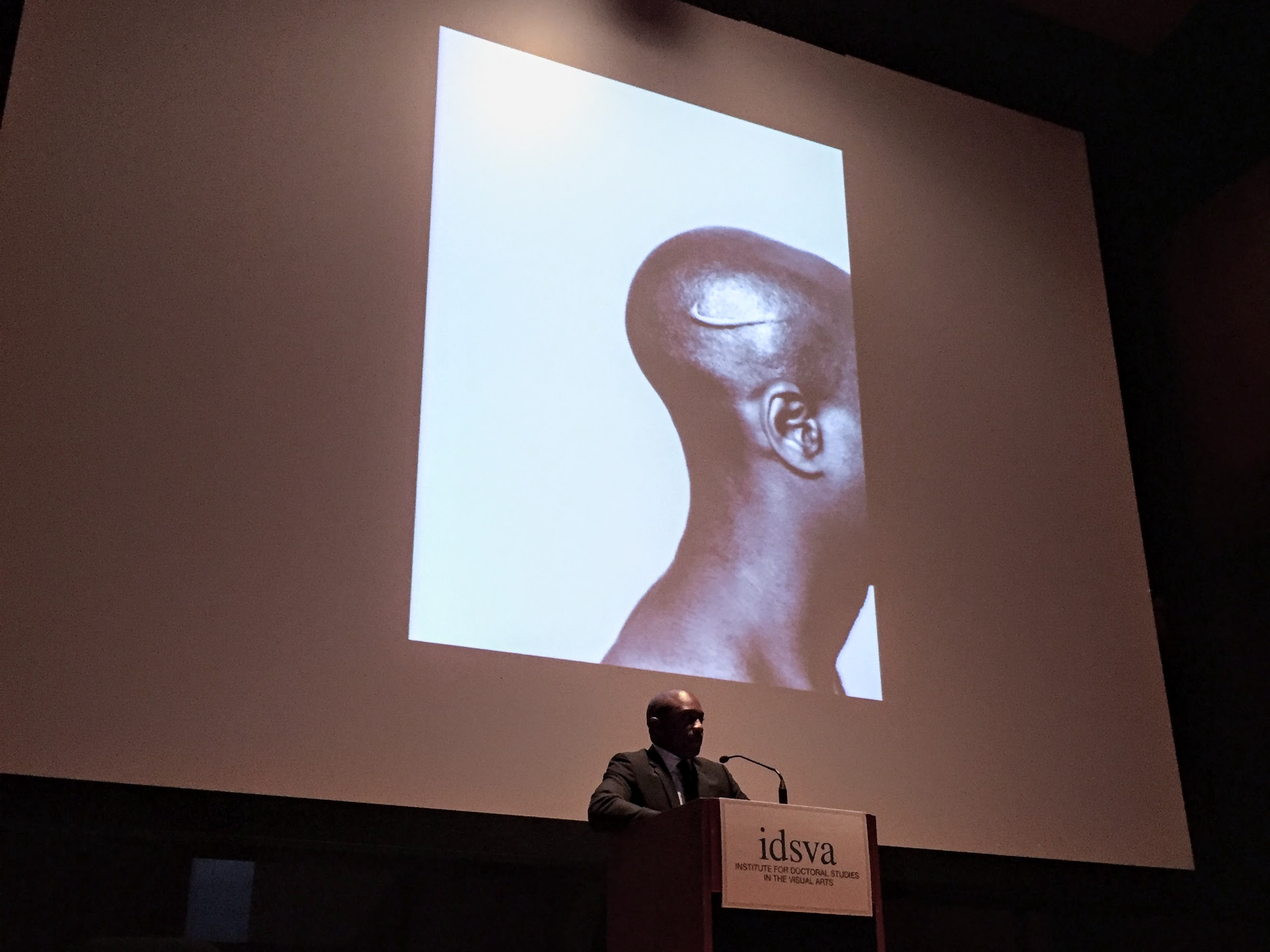 Hank Willis Thomas speaking at the 2017 IDSVA Commencement in NYC with his work  Branded Head , 2003, displayed. Photo by Simonetta Moro