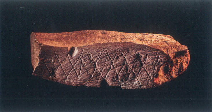 """An ochre stone with symmetrical cross-hatching etched on it 75,000 years ago was found in the Blombos Cave at the southern tip of Africa. The stone's patterned 'uniqueness' (as patterns are in our Universe's sea of chaos) suggests that the person etching the pattern realized how unlikely it would be seen as having spontaneously occurred by chance and, thus, intentionally did its etching in order to send a message to whomever might later discover it that a knowing """"Kilroy"""" [like you] once """"was here""""."""