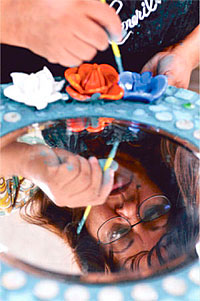 Carola Fernandez works on taking the grout out of the  roses on a circular mirror that she is making. Piece by  Piece is a nonprofit that teaches the homeless of Skid Row  and South L.A. to create beautiful mosaic artwork. Los  Angeles, CA 6/4/2010. photo by John McCoy