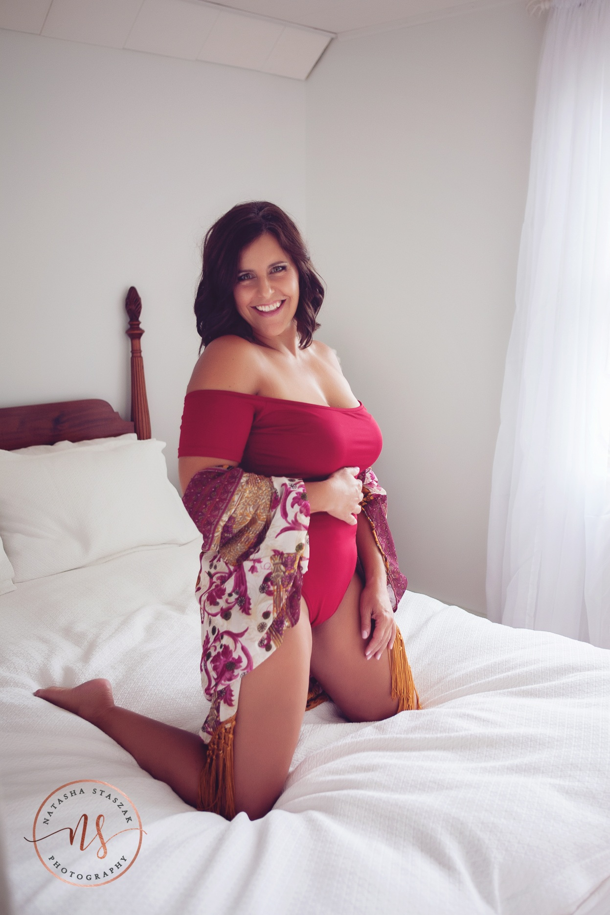 Is a Boudoir photo shoot on your bucket list? Buffalo Boudoir photography Natasha Staszak. Woman on bed red bodysuit.