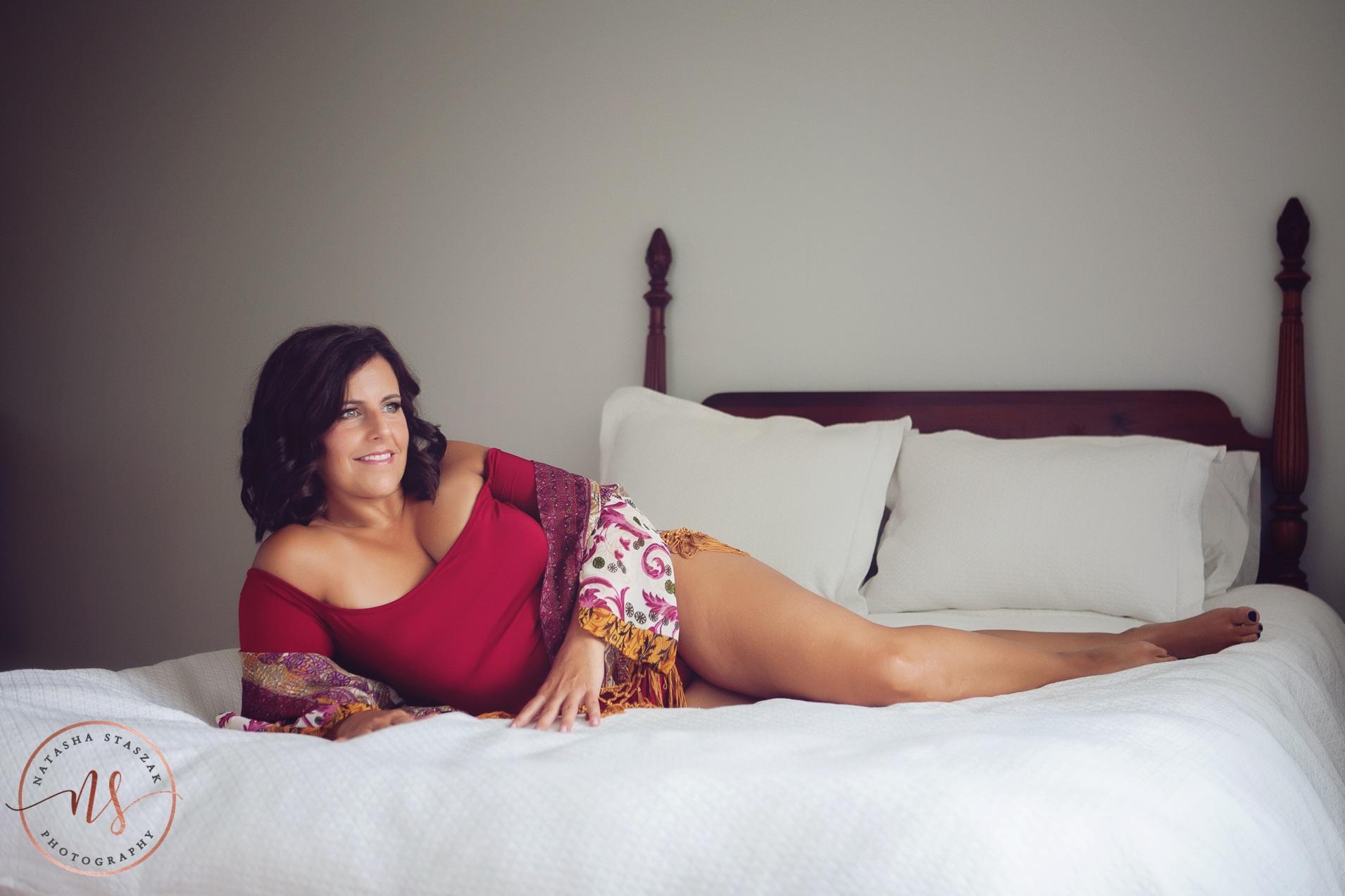woman lying down Buffalo Boudoir photo studio. Woman in red bodysuit.
