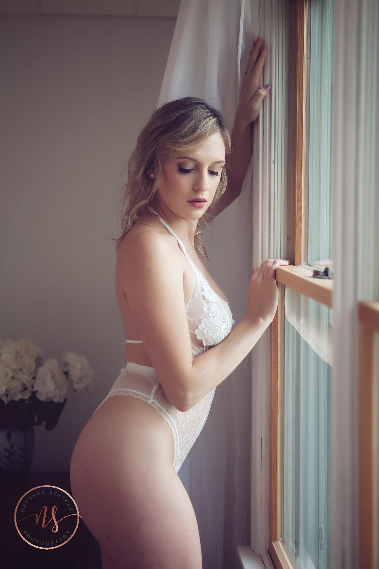 Boudoir Buffalo Photo shoot - white lingerie of woman standing near window.