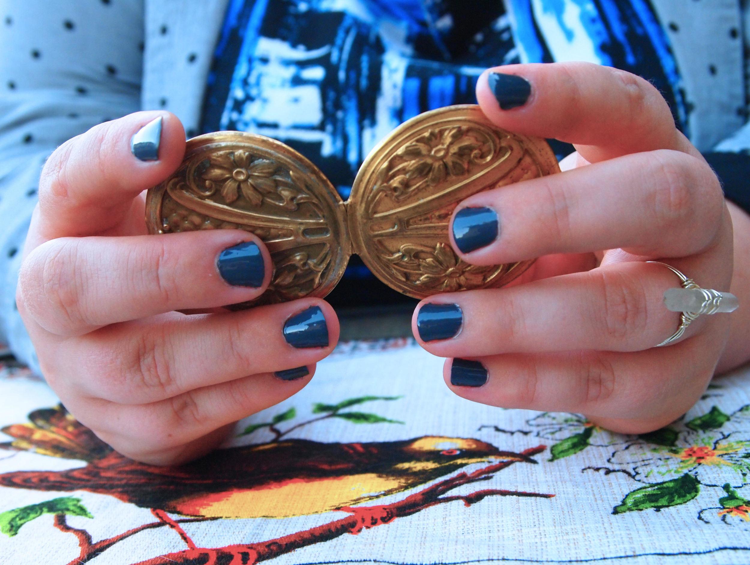 Tina's hands holding an antique locket.