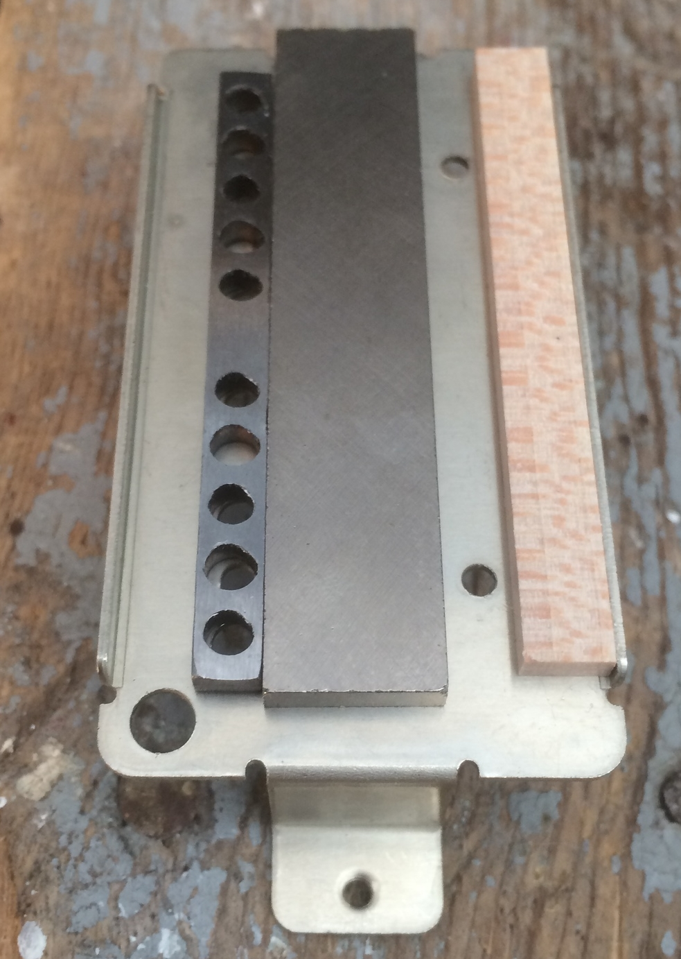 Here's the spacer, magnet and keeper laid out on the baseplate. You can see how the pole screws pass through the keeper. The space beside the magnet on the right is for the slugs and the maple spacer supports the bobbin. Notice on the far left there is a space for the braided shield conductor.