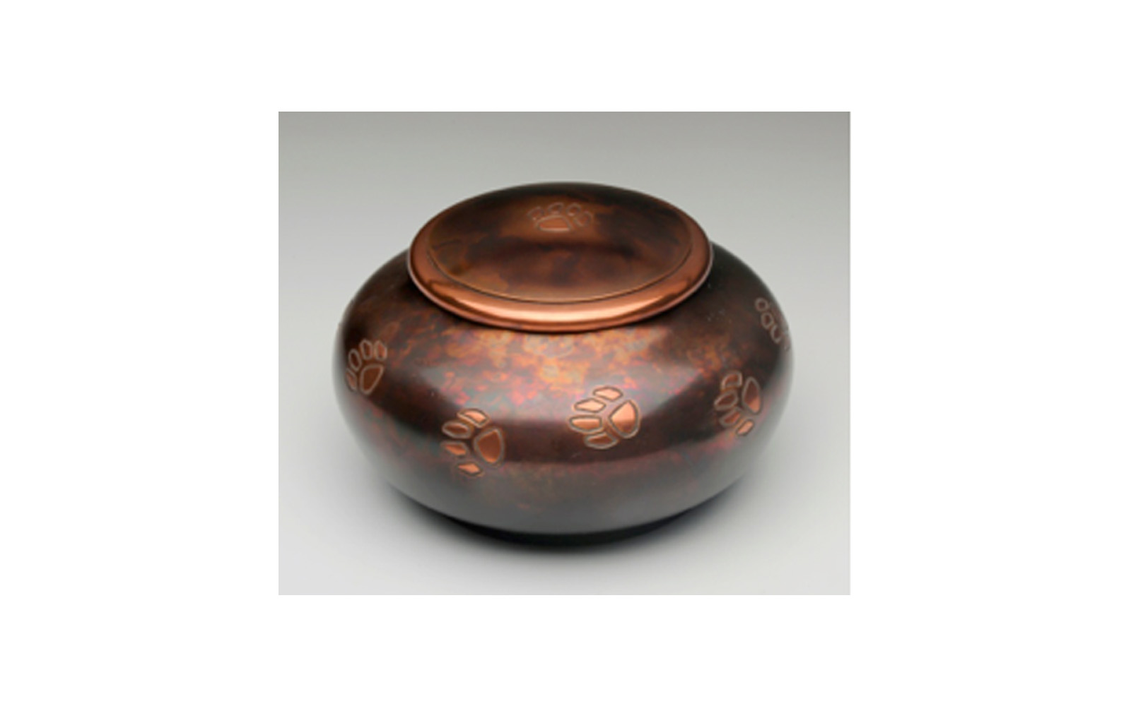 "Milano Raku Paw Print      Made of a Beautiful Brass with a Copper Overlay and a Raku Finish. This urn has a Threaded Lid and a Felt-Lined Base. This urn comes in Large, Medium, and Small sizes.     Large:  Measures 4.75"" L x 7.25"" W x 7.25"" H, 100 Cu. Inches, up to 95 lbs.,    $78      Medium:  Measures 4"" L x 6.5"" W x 6.5"" H, 70 Cu. Inches, up to 65 lbs.,    $60      Small:  Measures 5.5"" L x 5.5"" W x 3.25"" H, 45 Cu. Inches, up to 40 lbs.,    $50"