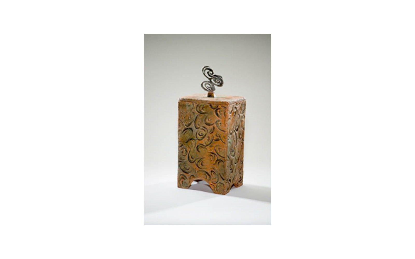 """Tempo Ceramic Urn   This ceramic urn has a steel designed handle that was used by the Artist to create the impressions on the sides of it. This urn measures 6 ¾"""" L x 6 ½"""" W x 15"""" H and holds 225 Cu. Inches, up to 225 lbs. $635    *Please Note: Each piece is uniquely made by its Artist resulting in different colors and weight"""