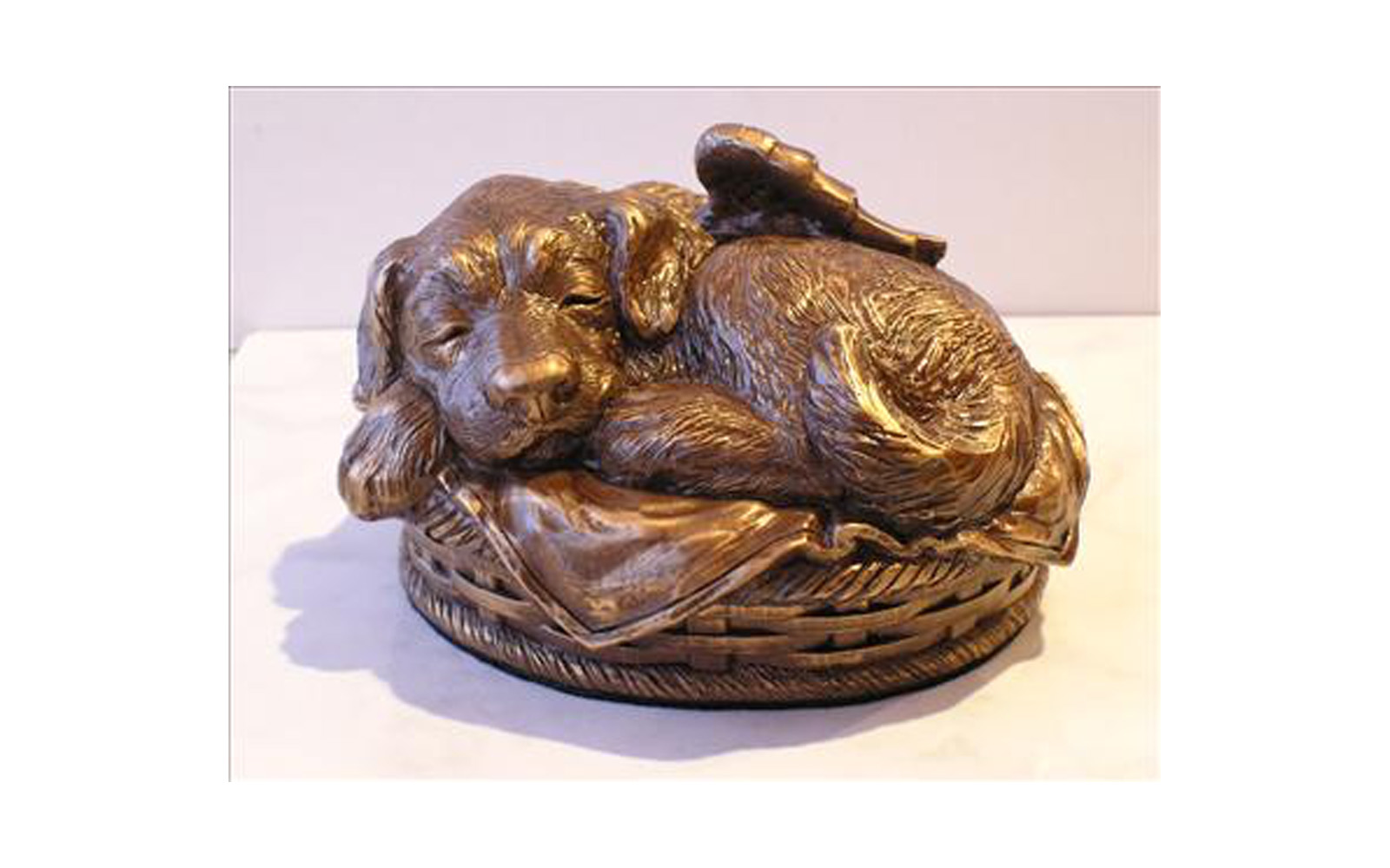 "Angel Dog Urn   Made of a cold cast bronze (polymer with bronze additive). This piece is available with a personalized laser engraved heart name tag on the collar. Cremated remains are stored through the bottom.   Small size measures : 7.5"" L x 6.5"" W x 4.5"" H, 50 Cu. Inches, up to 50 lbs.  Available in Black, White, Bronze, Verdigris, Metallic, Metallic with Bronze Finish, Metallic with Silver/Stainless Steel Finish, Metallic with Copper Finish colors.   $105  without engraving   $125  with engraving   Large size measures : 9"" L x 7.5"" W x 5"" H, 100 Cu. Inches, up to 100 lbs.  Available in Black, White, Bronze and Verdigris colors.   $125  without engraving   $145  with engraving"