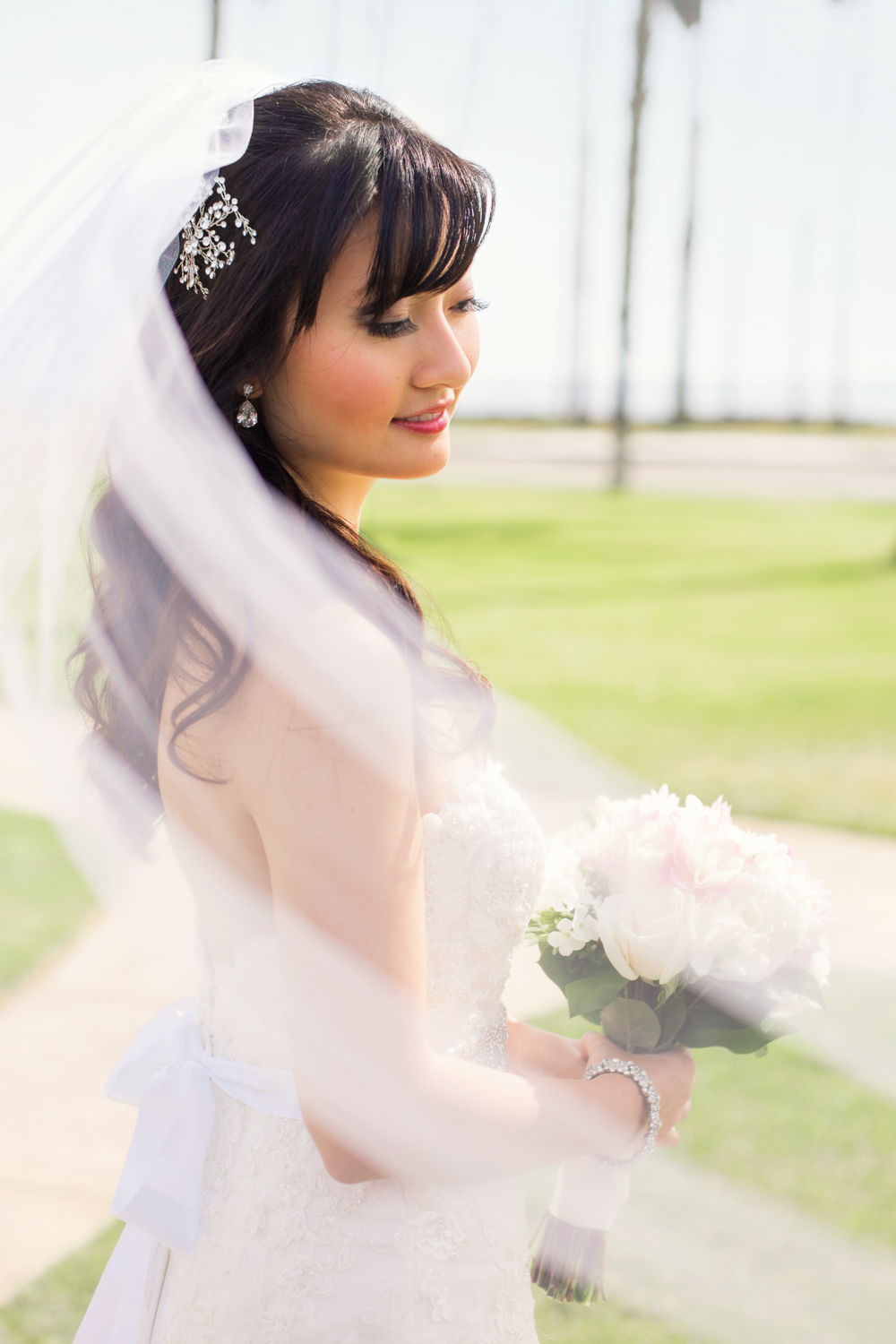 Bride portrait on the beach with veil and rose bouquet.
