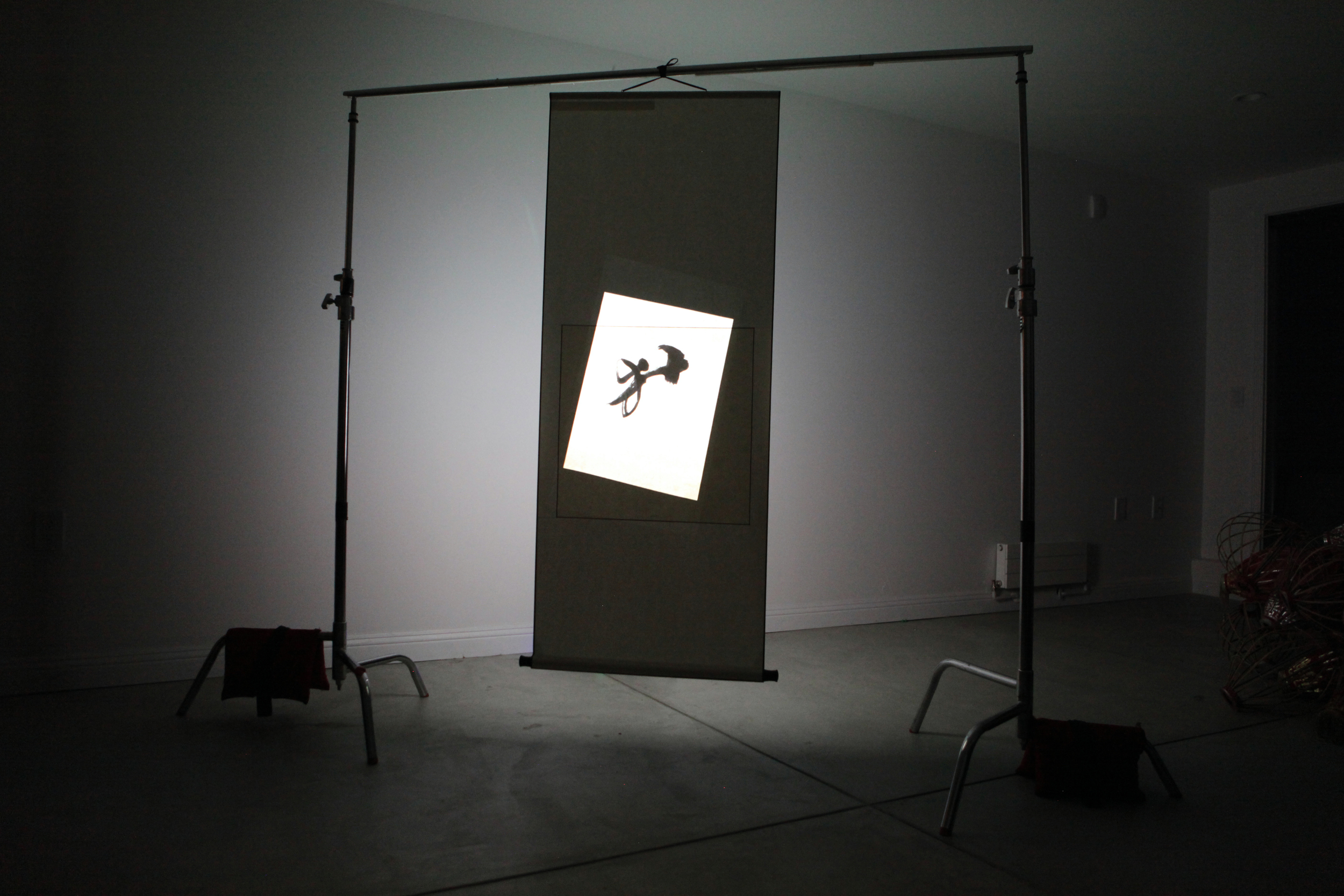 Calligraphy Abstraction  Projected video, two C-stands, red sandbags and aluminum  2014