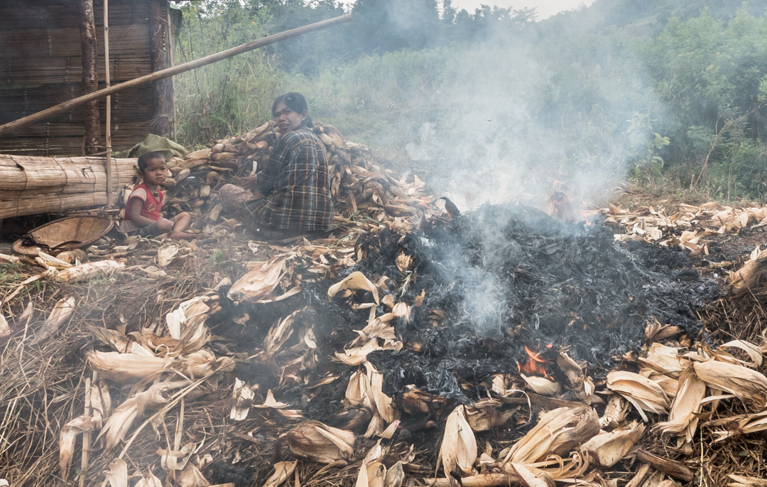 A woman peels corn all day with her baby alongside the smoking fire....