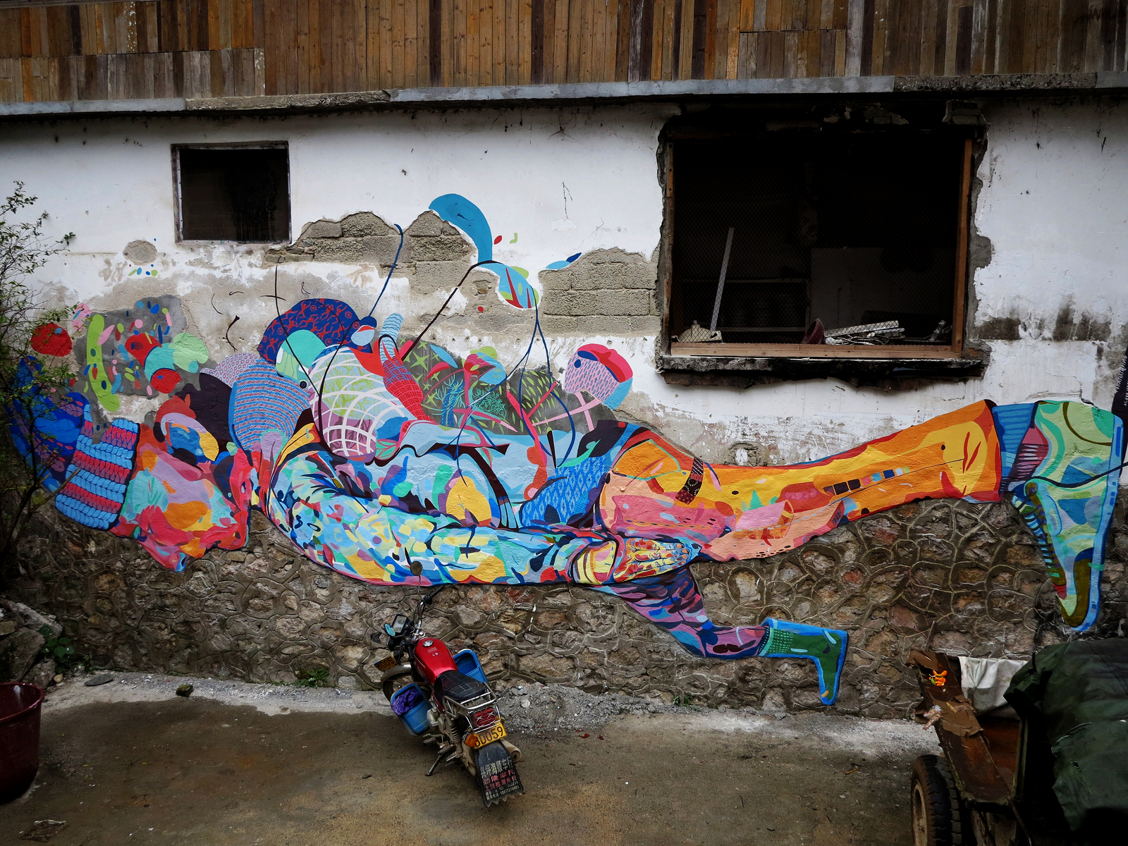 TRAVELLER,  XingPing, China, 2012  20x40', latex and cement  We cemented the uneven wall in the shape of the figure before painting with brush