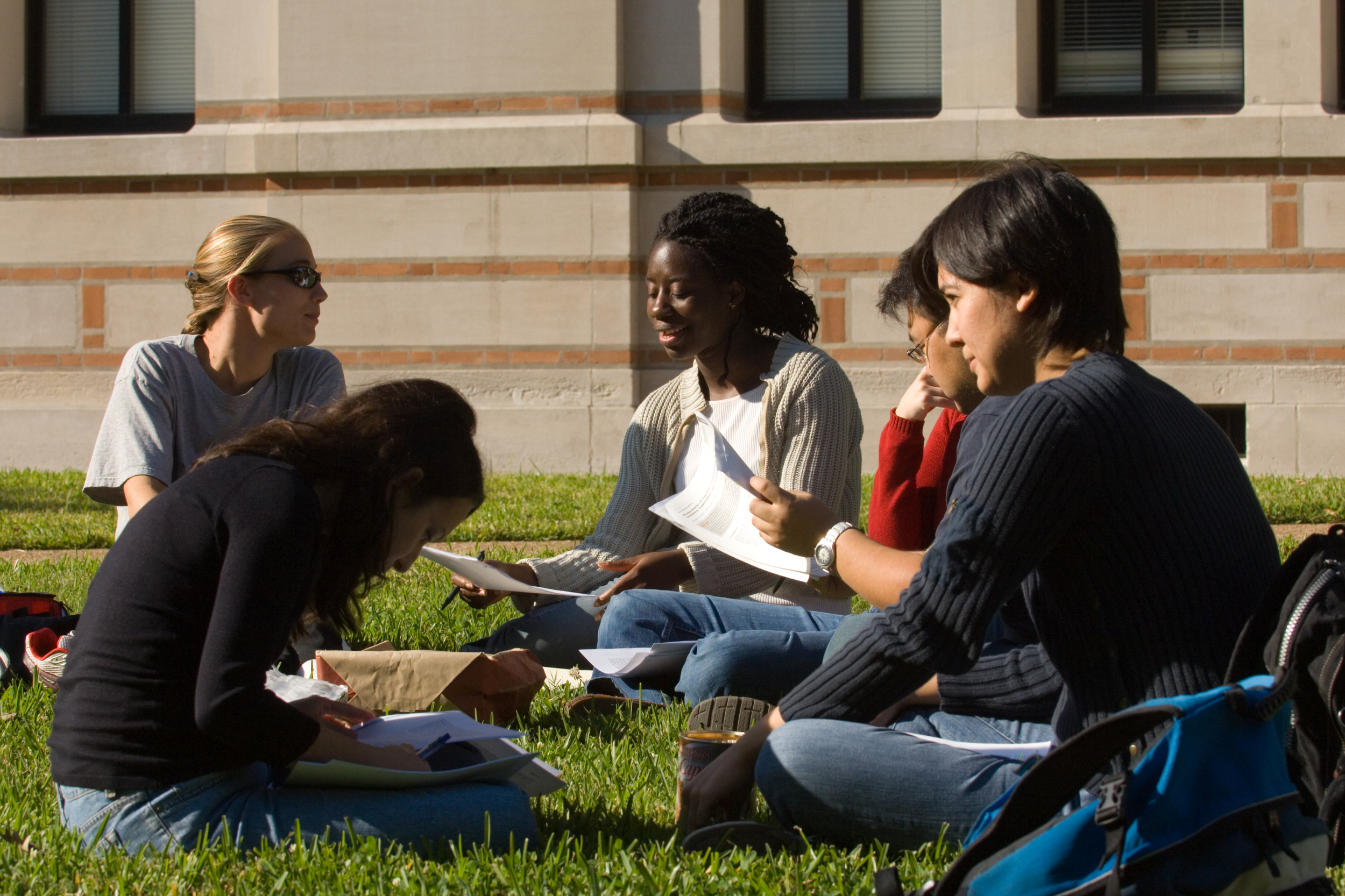 Rice University students sitting in the grass discussing papers.