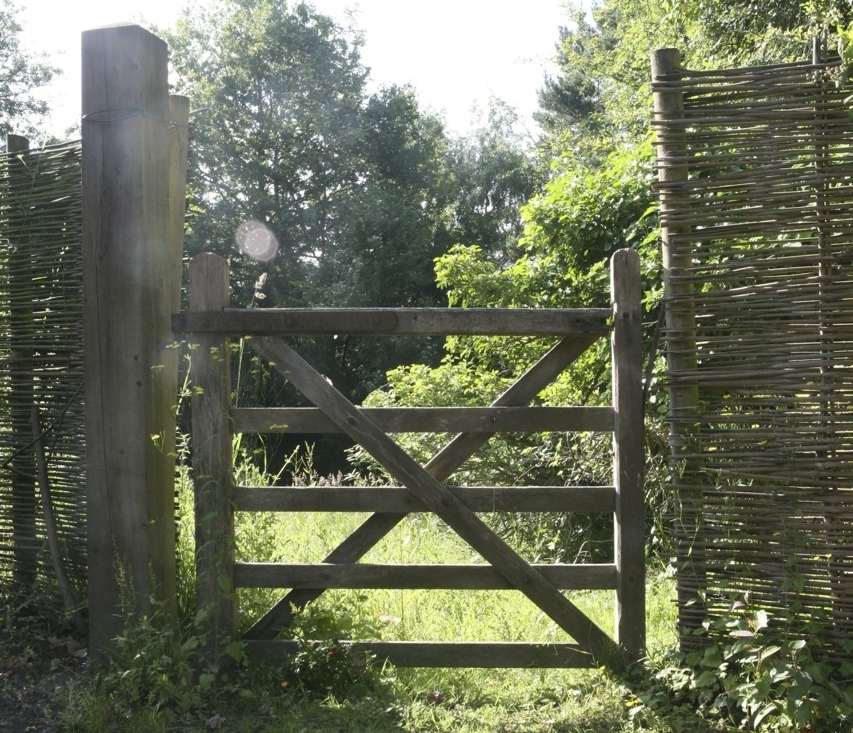 A simple wooden gate marks an entrance to the vegetable garden at Gravetye.