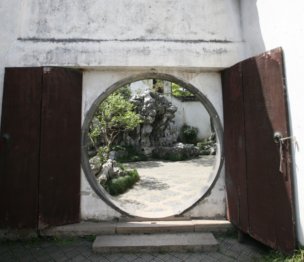 A moon gate provides an invitation into the garden.