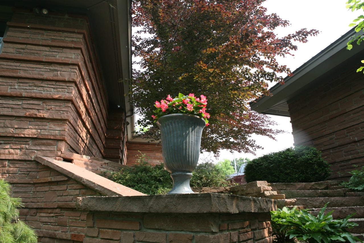 A ceramic urn filled with begonias calls our attention and draws us further into the garden.