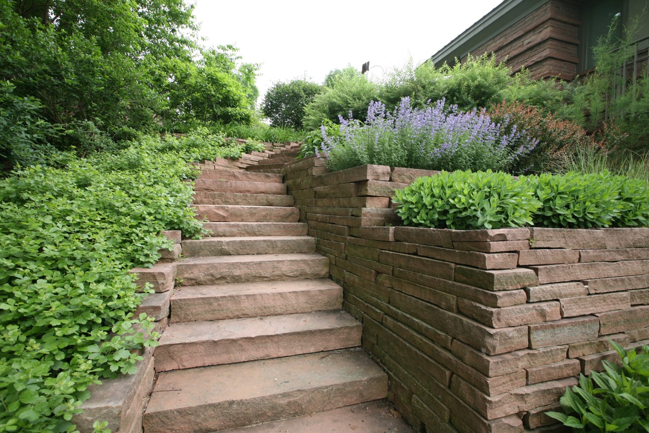 Stone steps and terraced planters take advantage of the natural slope.  Note how their simplicity adds to the overall composition.  Gro  -low sumac provides a connection to a more wild area below.