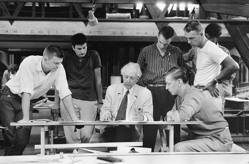 Frank Lloyd Wright with members of the Fellowship. Fragment of the famous quote can be seen in the background. Source: cargocollective.com