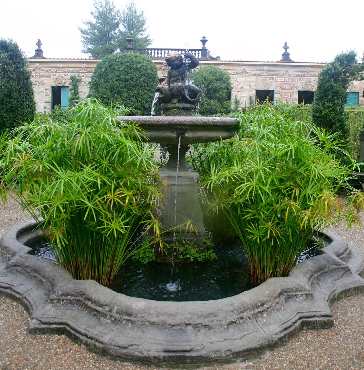 A mer-boy sits atop the central fountain. Water loving papyrus makes a bold statement. WHo thought vegetable gardens couldn't have style.