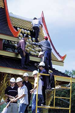 """Some of the university's Thai students help stack roof tiles.  Visitors were invited to sign their names on the backs of the tiles that now cover the roof of the pavilion. ""  Source: U of Wisconsin  (Photo:  Michael Forster Rothbart )"