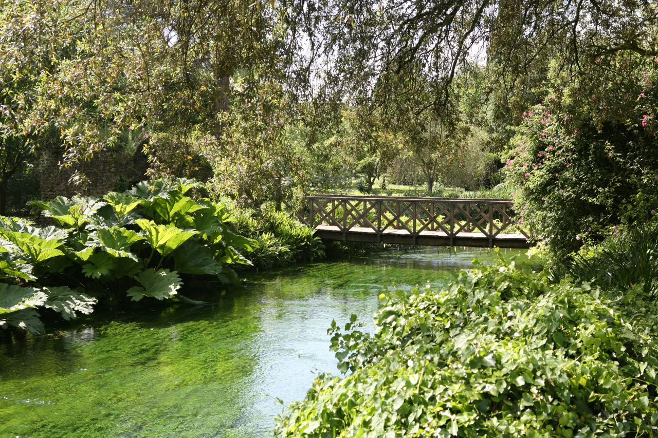 The river Ninfa flows along the southern border of the garden. Bridges connect to the broader preserve land.