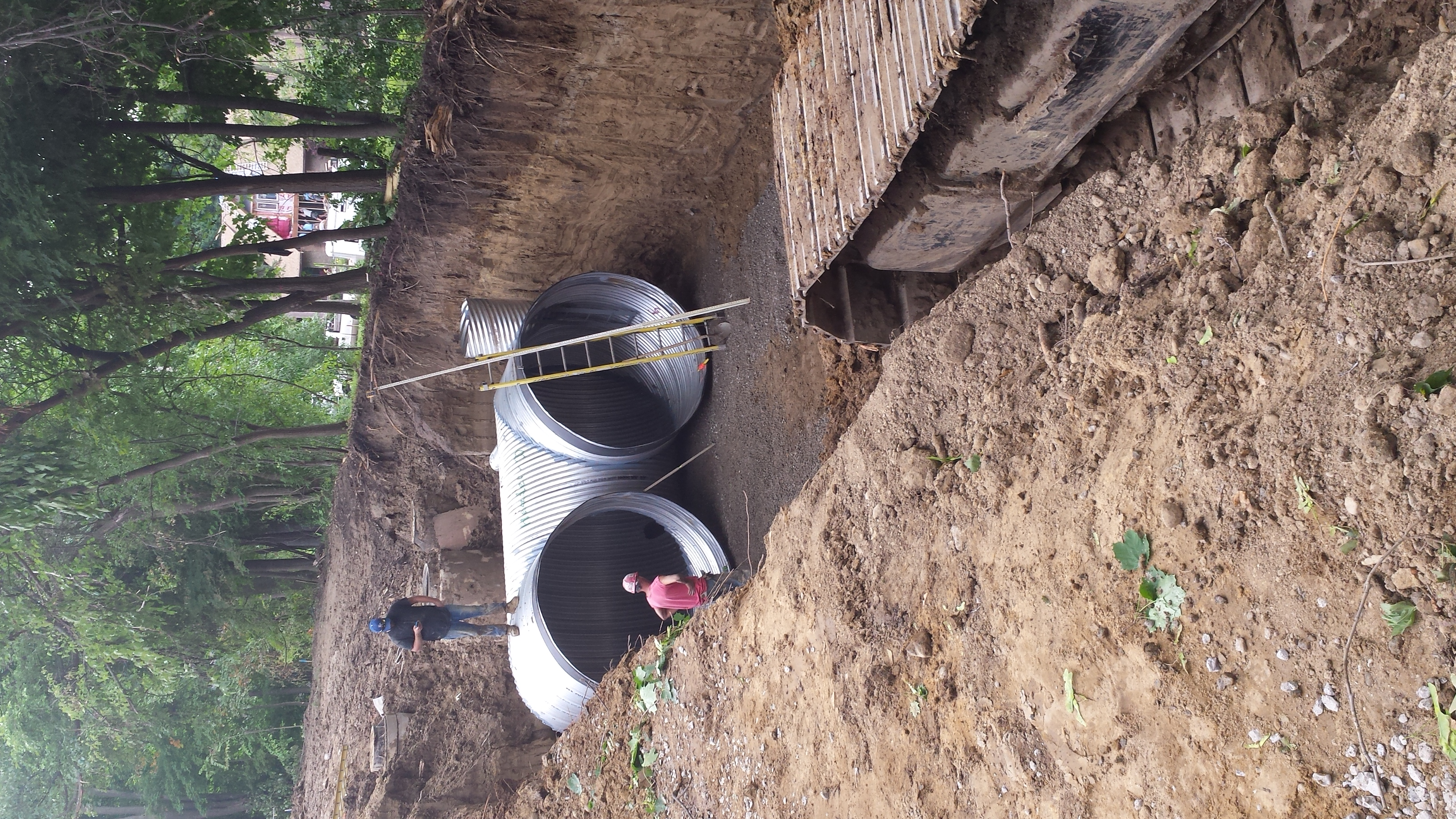 These 8' diameter pipes set below deep in the ground will hold storm water surges and slowly empty after a storm