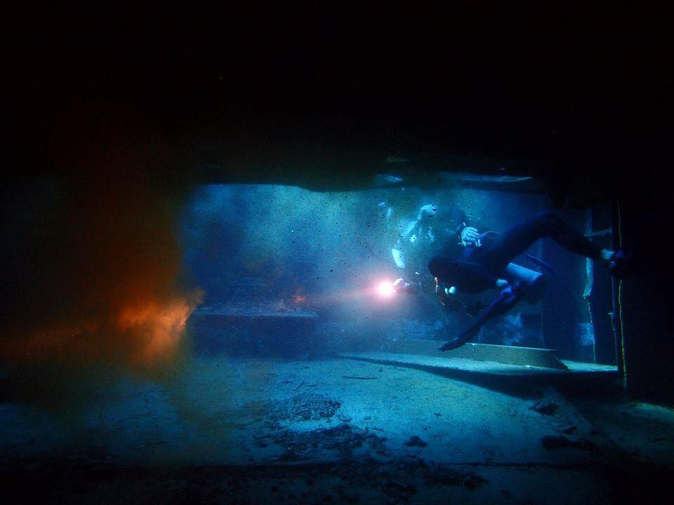 A diver investigation the inside of the Glenn Nusa